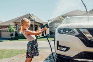 Photo of a Little Girl Washing a Car